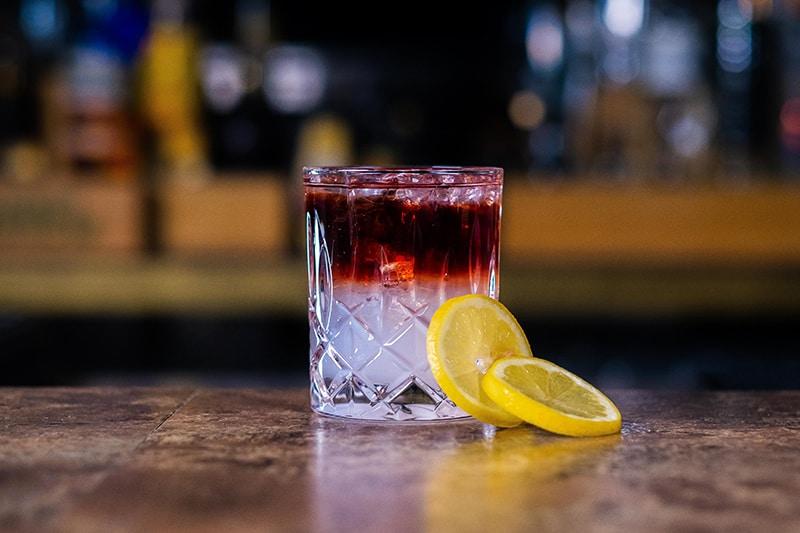 primitivo-cocktail-auf-bartresen-mit-zitronen